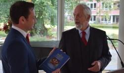Grootmeester Gerrit van Eijk overhandigt het boek 'Magie van de loge' aan burgemeester Sjoerd Potters.