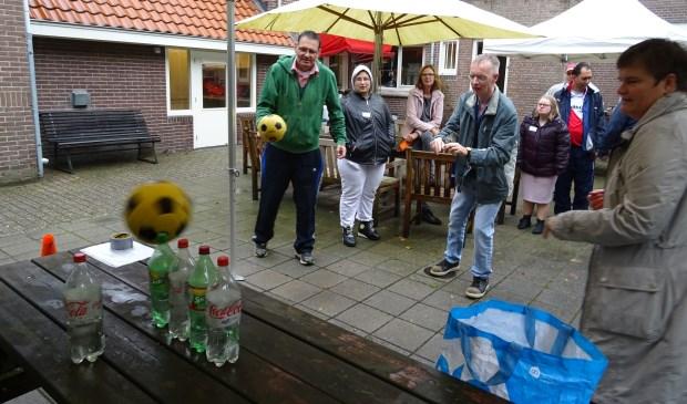 Onder aanmoediging van spelbegeleider en wethouder Anne Brommersma probeerden de deelnemers in drie worpen zoveel mogelijk flessen van de tafel te gooien.