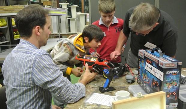 V.l.n.r. Vader Rene kijkt hoe zijn zoon Salomé samen met reparateurs Pieter en Roel de radio bestuurbare auto onderzoekt. (foto Frans Poot)