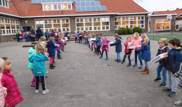 Kinderen van de Groen van Prinstererschool geven de gevulde dozen door op weg naar kinderen die het veel minder hebben.