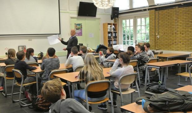 Frans Poot bespreekt met de leerlingen de door hen geschreven teksten.