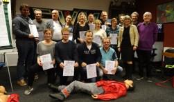 Trots tonen alle deelnemers aan de cursus Eerste Hulp bij Sport en Reanimatie hun certificaat. Rechts docent Jan Broers en wethouder Madeleine Bakker, die de certificaten heeft uitgereikt.