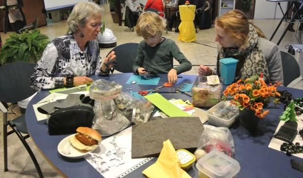 Siem maakt aan de knutseltafel, onder toeziend oog van vrijwilliger Truus, figuurtjes uit gerecycled materiaal.