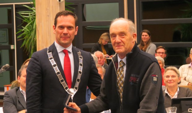 Burgemeester Sjoerd Potters reikt Nico Jansen de Chapeaupenning van de gemeente De Bilt uit.