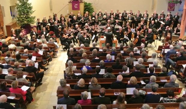 Het koor, orkest en solisten in een volle kerk