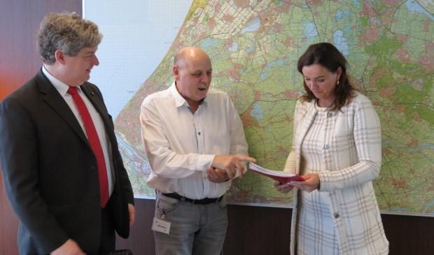 Onder toeziend oog van gemeenteraadslid Christiaan van Nispen tot Sevenaer overhandigt Herman Kramer de handtekeningen aan gedeputeerde Jacqueline Verbeek.