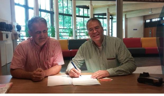 Peter Schlamilch (rechts) ondertekent de inschrijving van Forza bij de gemeente.