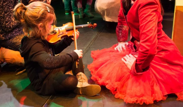 De kinderen worden uitgenodigd om dicht bij de muzikanten en de instrumenten te komen.