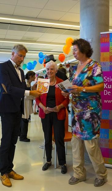 Wethouder Hans Mieras krijgt uit handen van (v.l.n.r. Ellen Thier en Joke Lith het SKC-programma 2017-2018 uitgereikt. (foto Kees van Gogh)