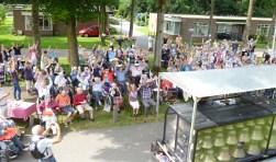 Het publiek geniet volop van het concert in de tuin van d'Amandelboom.