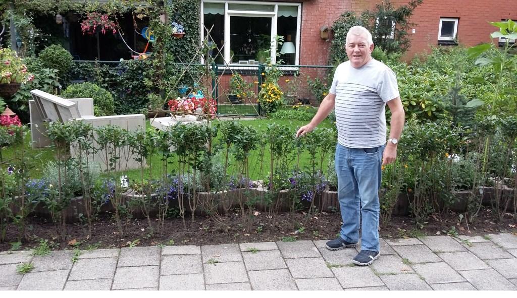 Pieter Pols voor zijn fraaie tuin met bloemen, gras en bank.