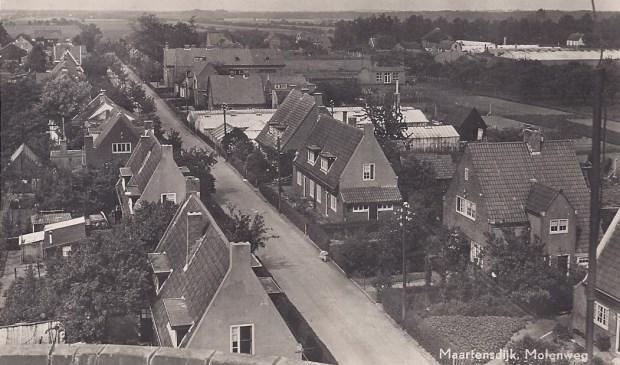 Deze foto van de Maartensdijkse Molenweg is genomen vanaf molen De Hoop en toont de in 1922 gebouwde 10 huizen voor mensen met 'huwelijksvoorrang'. Verder zijn de kassen van van der Heijden en de School met den Bijbel zichtbaar.