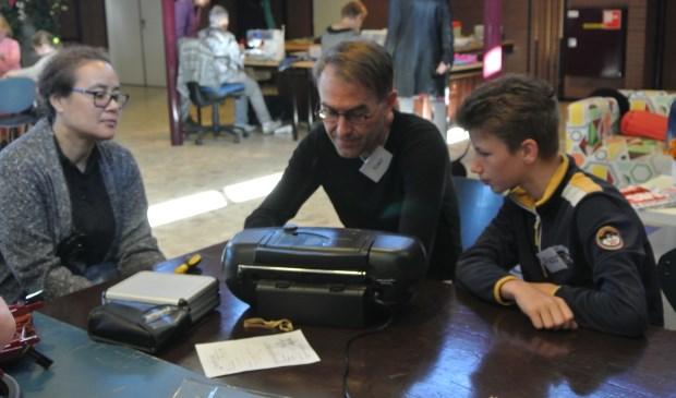 Reparateur Koert (midden) kijkt een radio-cd speler na met hulp van stagair Pieter (rechts). Op de achtergrond verstellen naaisters Magda en Tiny kleding. (foto Frans Poot)