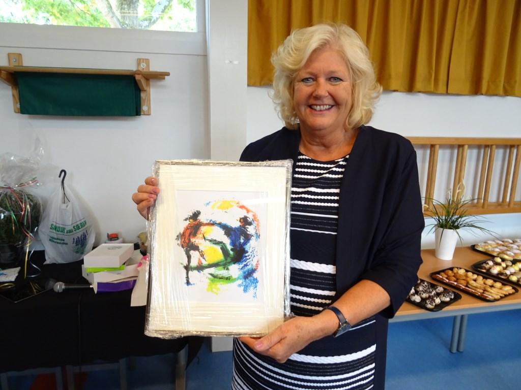 Trots toont Els Roozenbeek de litho van Jits Bakker, die zij van Stichting Delta als afscheidscadeau kreeg.   © De Vierklank