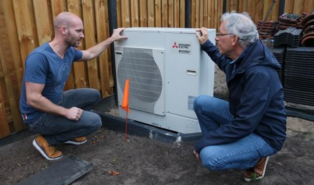 Energieambassadeur Frans den Braber (r) en bewoner Bram de Deugd (l) bekijken de buitenunit van de warmtepomp bij de energieneutrale woning aan de Waterweg in De Bilt. (foto: Jenny Senhorst)