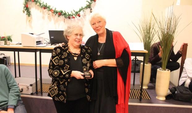 NBB-Afdelingsvoorzitter Barbara van Dijk-Hage (rechts) overhandigt een verbouwereerde Elly Akkerman een 'Kei' van een onderscheiding.