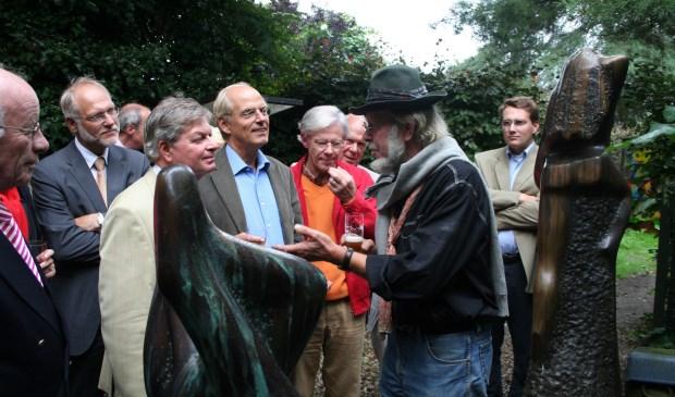 Jits Bakker leidt een delegatie rond in de beeldentuin.