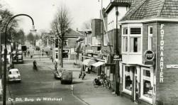 Deze foto uit 1959 (Burg, de Withstraat 8 en hoger) toont rechts het oude postkantoor dat in 1912 naar de Burg. de Withstraat verhuisde en hier bleef tot einde jaren zestig. Toen deze foto genomen werd, was het nog een echte winkelstraat.