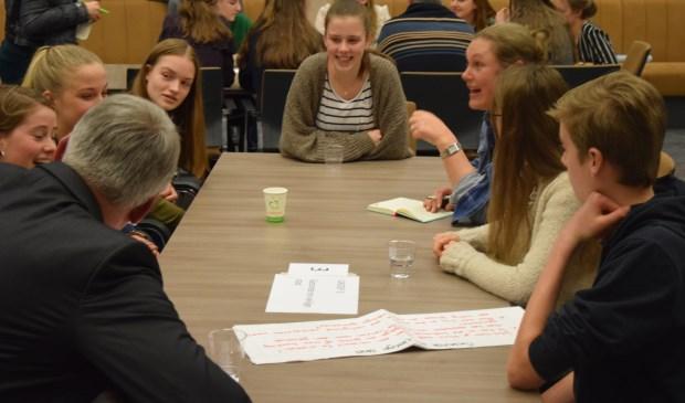 Leerlingen en lijsttrekkers met elkaar in gesprek.