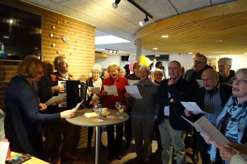 De jubilaris tussen de zangers van AZM die een prachtig feestlied ten gehore brachten.   © De Vierklank