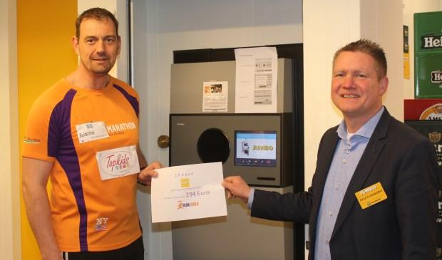 Nico Sturkop en Jelle Farenhorst bij het nieuwe apparaat van Jumbo met de cheque van bijna 300 euro, die de klanten al aan KIKA doneerden.