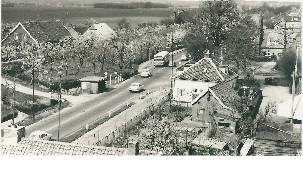 Deze foto van het kruispunt bij het voormalig gemeentehuis van Maartensdijk is in de jaren zestig van de vorige eeuw door wijlen Jaap Eits vanaf de brandweertoren gemaakt. De fruitbomen bij de hoeve Persijn van boer De Rooij staan al in bloei, terwijl de kastanjeboom voor het gemeentehuis nog aan de lente moet beginnen. De foto is voor 1968 gemaakt, want de Tolakkerweg is nog niet verbreed. Wim de Rooij vertelde, dat in augustus 1968 van zij
