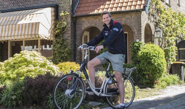 Job Paauw op een e-bike voor het huis van zijn ouders, waar hij zijn bedrijf begonnen is.