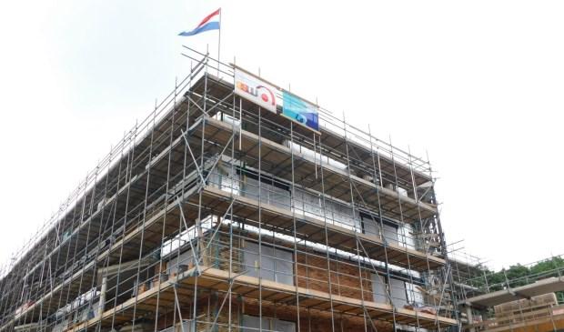 Vlaggen sieren de top van het nieuwe appartementengebouw De Leijen Zuid.