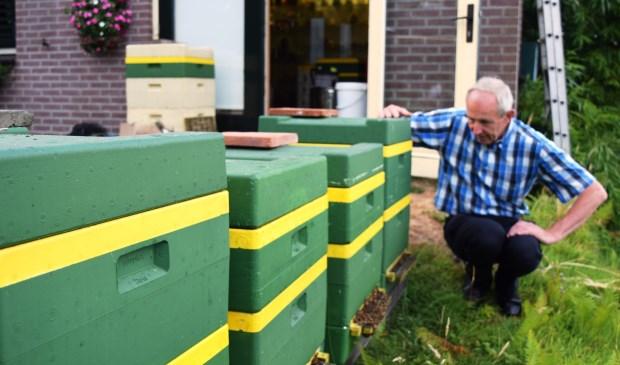 Aart van der Linden met een paar van zijn bijenkasten.