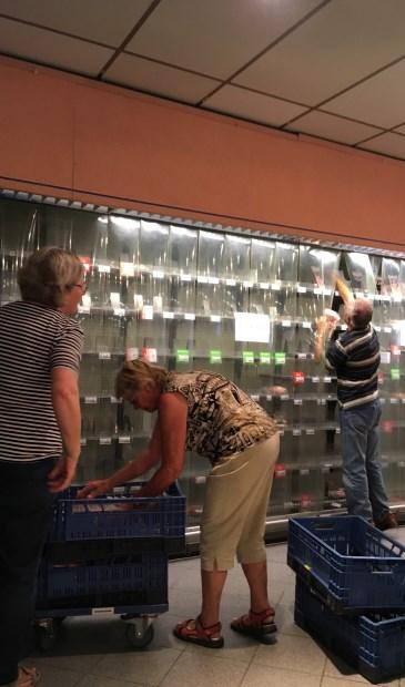 Medewerkers van de Voedselbank helpen de schappen van Albert Heijn leeg te maken.  Foto: Voedselbank © De Vierklank