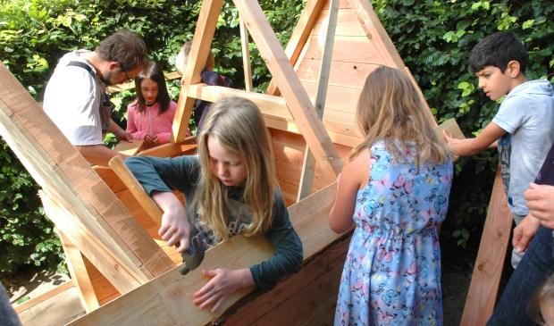Groep 5 is geconcentreerd bezig met de bouw van een speelhuisje.