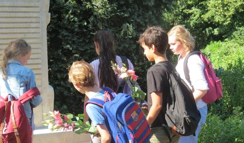 Leerlingen van de Groen van Prinstererschool leggen bloemen bij het monument.