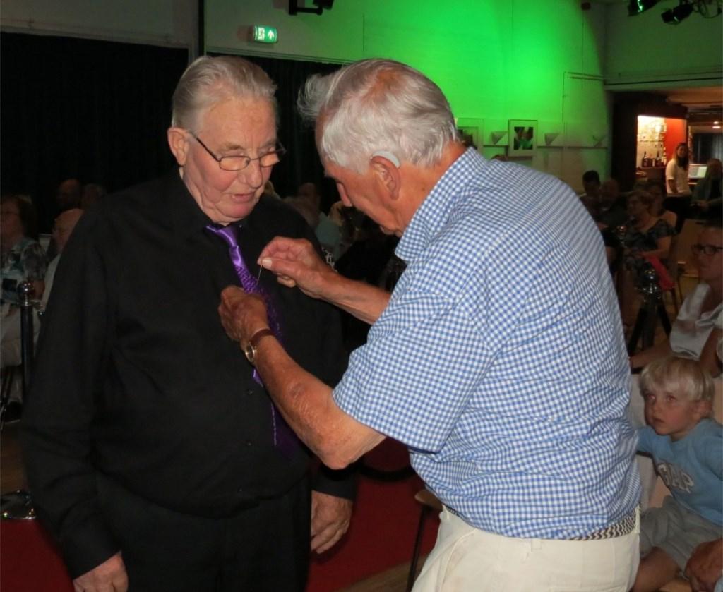 Mystery guest Henk Veenstra speldt het insigne op bij Kees Bos voor zijn 70 jarig jubileum.  © De Vierklank