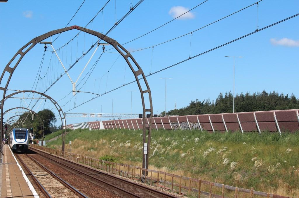 Vanaf het perron in Hollandsche Rading zijn de hoge lichtmasten (in het midden van de A27) die ruim boven het geluidsscherm, de trein en de unieke spoorbogen uitsteken, goed te zien.     © De Vierklank