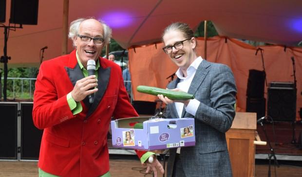 Wethouder Dolf Smolenaers krijgt tijdens de opening een doos komkommers.   © De Vierklank