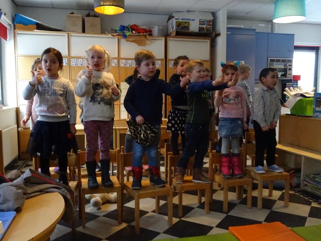 Leerlingen uit de groepen 1 en 2 zingen heel enthousiast hun liedjes voor alle aanwezigen. Het jongetje in het midden ging na het zingen met de pet rond.  © De Vierklank