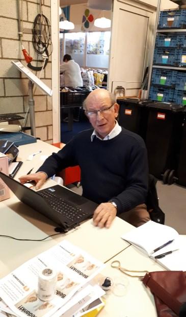 André Schellart, secretaris van de Voedselbank druk doende van achter zijn laptop.