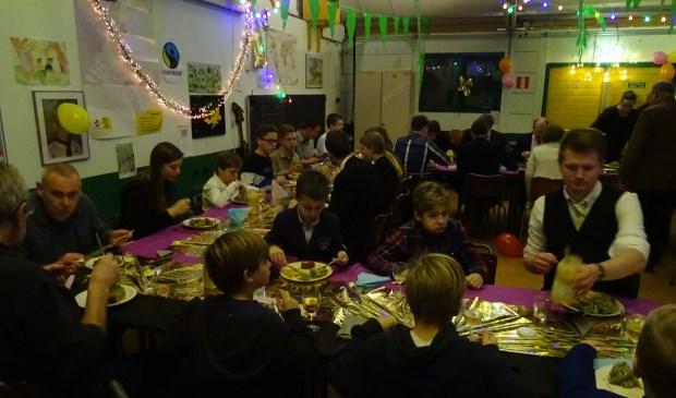 Iedereen geniet van de heerlijke boerenkoolmaaltijd in het feestelijk versierde scoutinggebouw.
