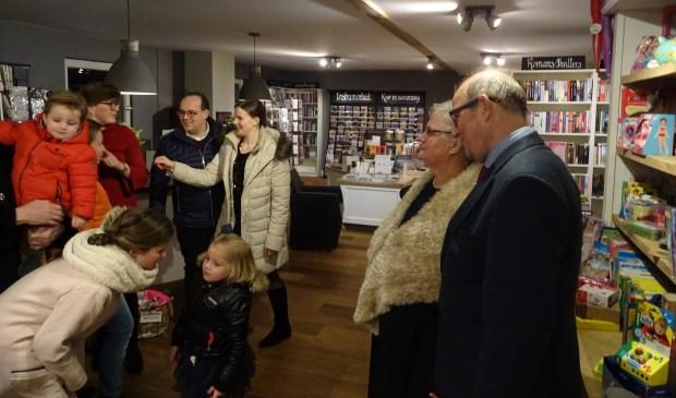 Henrieke (rode jurk) en Johan van den Berg (zwarte jas) met beide ouders Ineke en Jan van den Berg genieten van de vele bezoekers bij de feestelijke opening van de winkel.