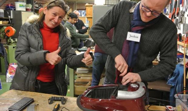 Ditte is blij want reparateur Jochem krijgt haar stofzuiger weer aan 't werk. (foto Frans Poot)