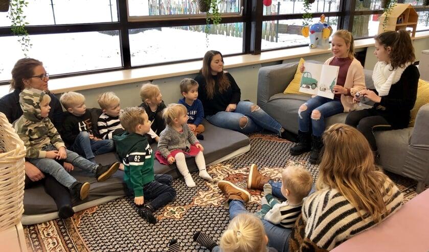 Leerlingen uit groep 6 lezen voor aan de peuters.