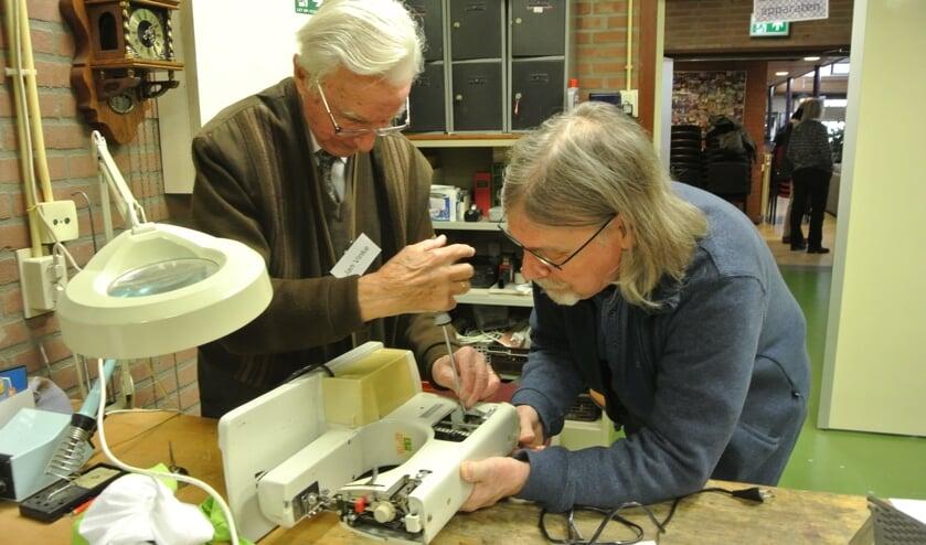 Jan Vinke repareert, samen met de eigenaar, een naaimachine. ( Foto Frans Poot)