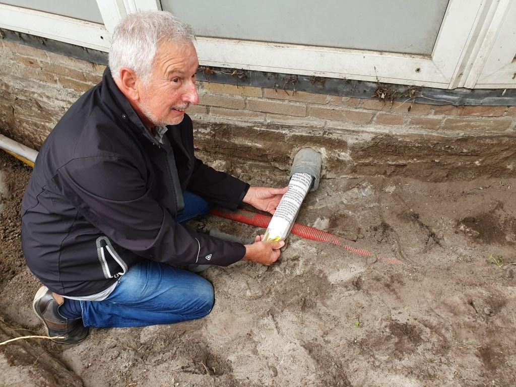 Voormalig directeur Henk Smits haalt de tijdcapsule uit de muur.  © De Vierklank