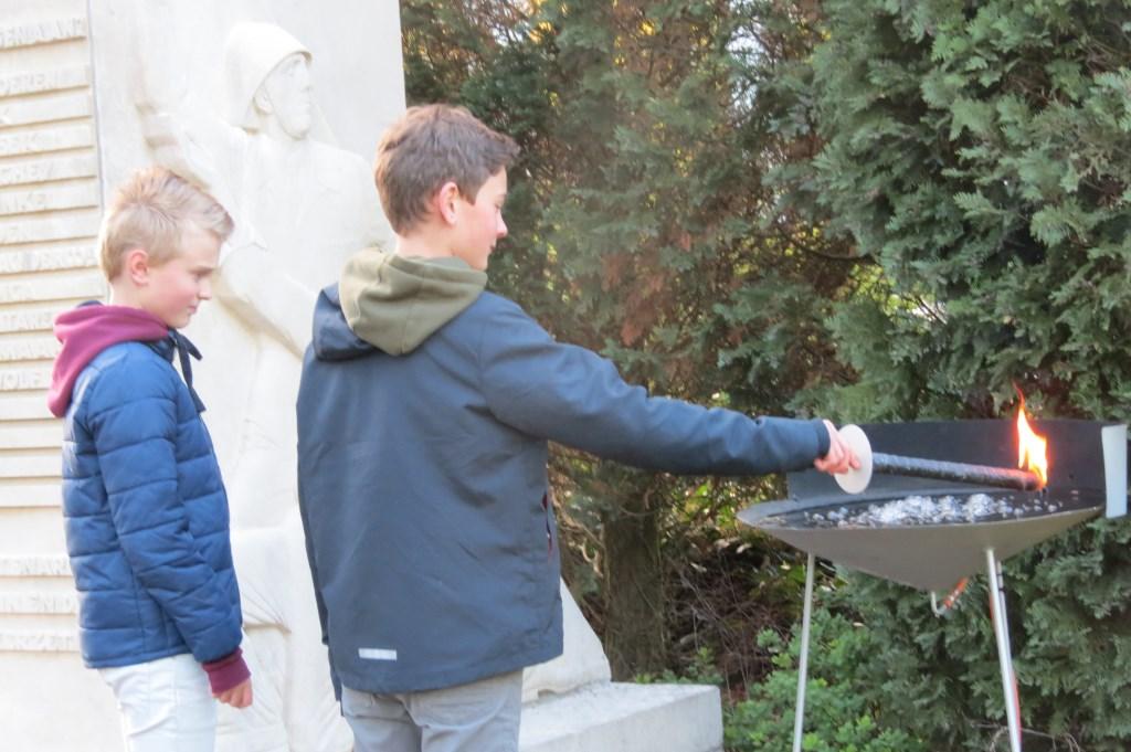 Jeremy en Etienne van de Groen van Prinstererschool ontsteken het herdenkingsvuur.  © De Vierklank