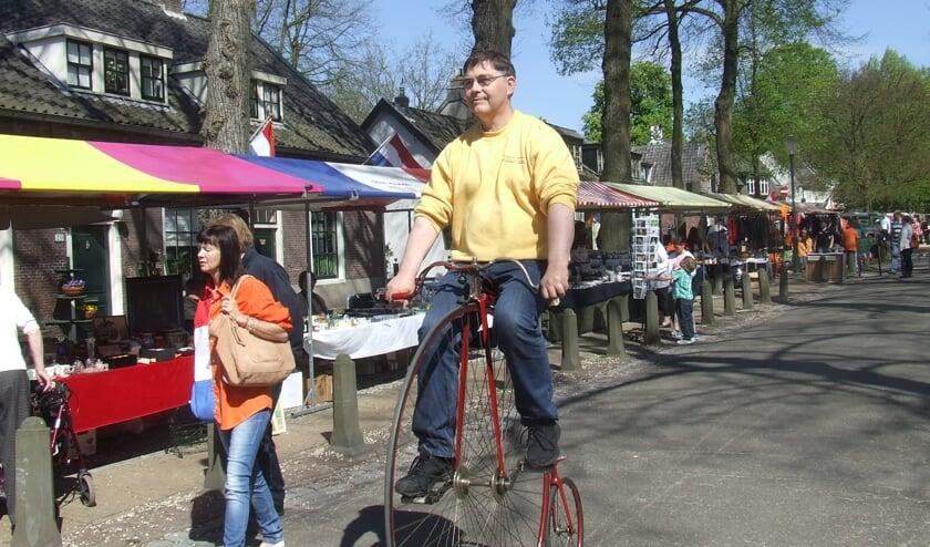 Koos Smits demonstreert op Koninginnedag 2012 een oude tweewieler uit zijn collectie.