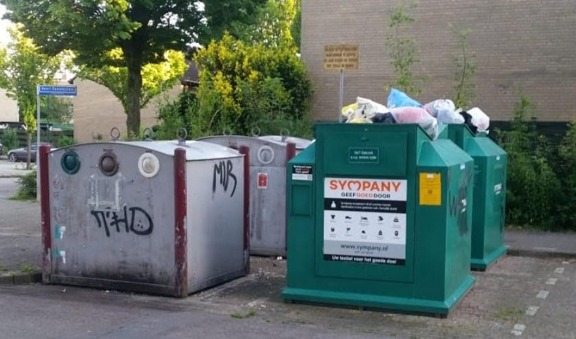 De textiel-containers tegenover de voormalige Aldi-winkel puilen uit; een lelijk gezicht en een gevaar in een verder mooie wijk.