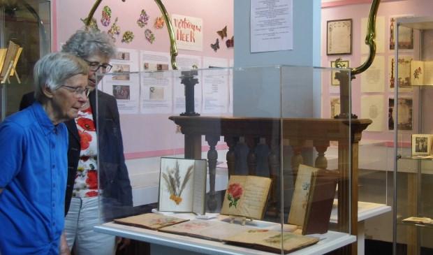 Hiety Grimm en Marry Veldhuizen bekijken de poëziealbums in de vitrine.  © De Vierklank