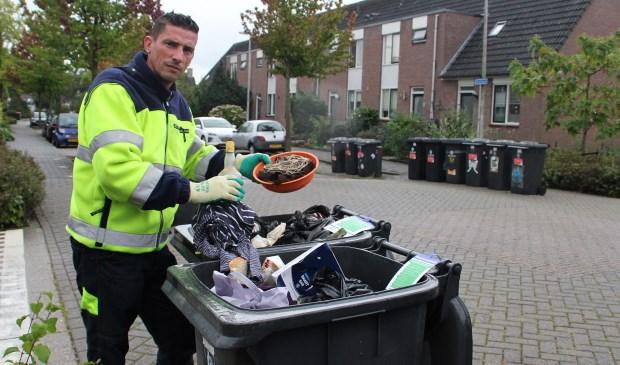 • Jan van der Grijn toont 'verkeerd' afval in enkele PMD-containers in Groot-Ammers. Foto: Bert Bons