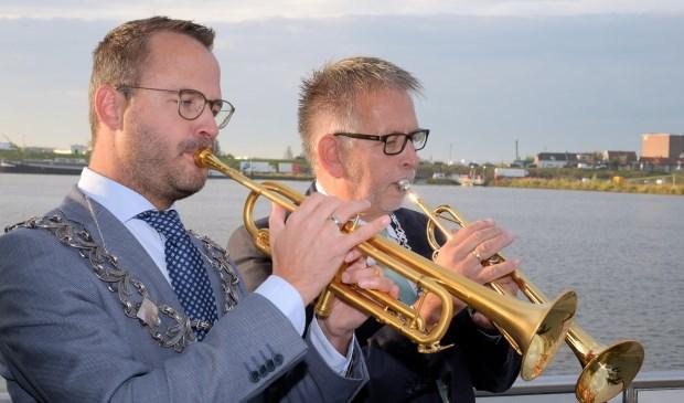 • Burgemeester Laurens de Graaf van Lopik (links) en de Zederikse locoburgemeester Maks van Middelkoop maken samen muziek op de Lek.