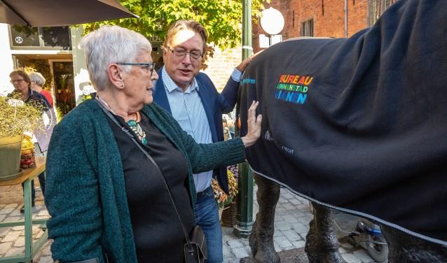 • Wethouder Frank Meurs en oud-wethouder Thea Schaafsma leggen een deken op het bronzen beeld 'Het Paard', dat deze week weer teruggeplaatst is na de afronding van de bestratingswerkzaamheden aan de Voorstraat.